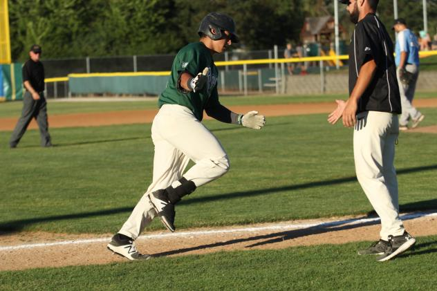 AJ Miller of the Medford Rogues high fives third base coach Mike Takamori after Miller's home run