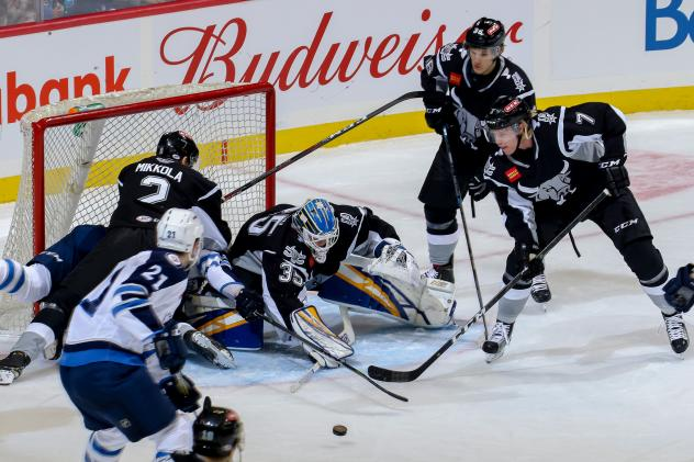 The Manitoba Moose and San Antonio Rampage scramble in front of the Rampage net