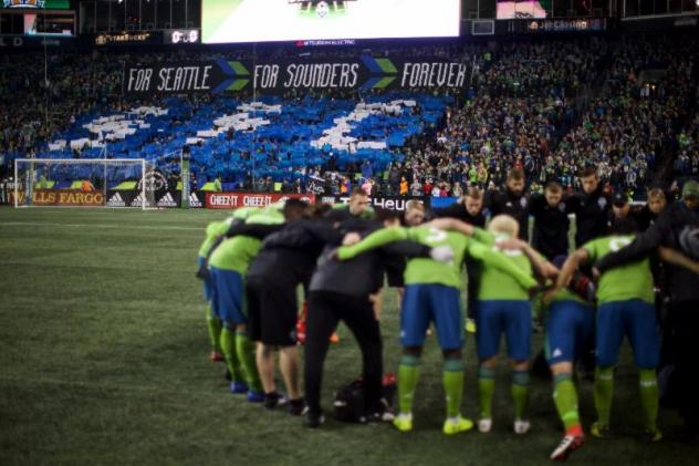 Seattle Sounders FC huddle in front of the Seattle crowd