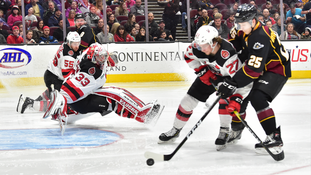 Binghamton Devils right wing Marian Studenic (27) shields the Cleveland Monsters while goaltender Cam Johnson dives into position