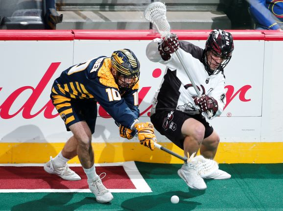 Alex Crepinsek of the Georgia Swarm (left) fights for a loose ball against the Colorado Mammoth