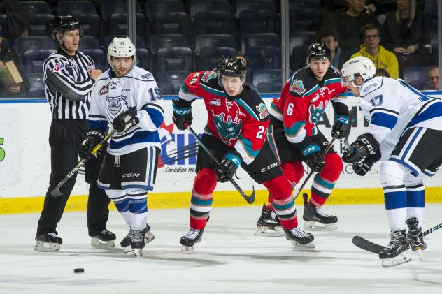 Kelowna Rockets centre Kyle Topping (center) eyes a loose puck against the Victoria Royals