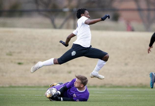Cordell Cato of OKC Energy FC leaps over the Louisville City FC keeper in a preseason game