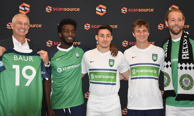 Scansource CEO Mike Bauer (left) and Greenville Triumph Chief Brand Officer Doug Erwin (right) with players