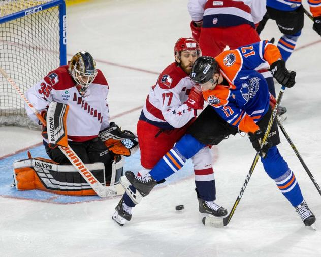 Allen Americans goaltender Lukas Hafner and forward Duggie Lagrone attempt to keep the Tulsa Oilers at bay
