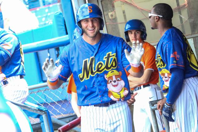 Tim Tebow reacts in the Syracuse Mets dugout to getting the silent treatment from his teammates after hitting his first career Triple-A home run