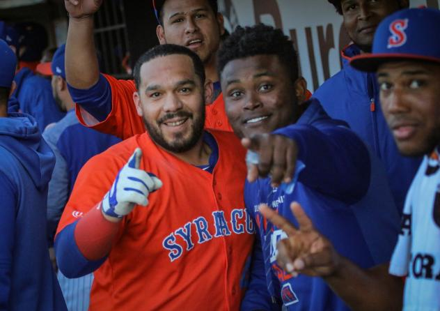 Rene Rivera celebrates in the Syracuse Mets dugout with his teammates after his first-inning home run on Friday night