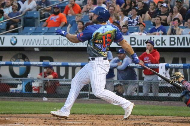 Tim Tebow of the Syracuse Mets (in SpongeBob SquarePants jersey) watches his home-run ball fly over the center-field wall