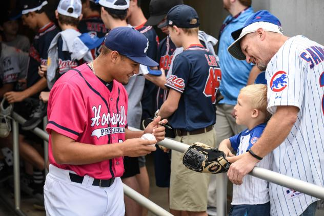 Jovani Moran of the Pensacola Blue Wahoos signs an autograph for a young fan