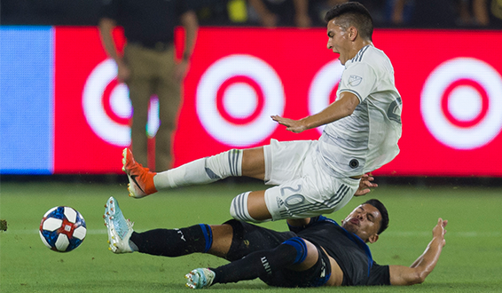 Andres Rios of the San Jose Earthquakes (bottom) makes a tackle against LAFC