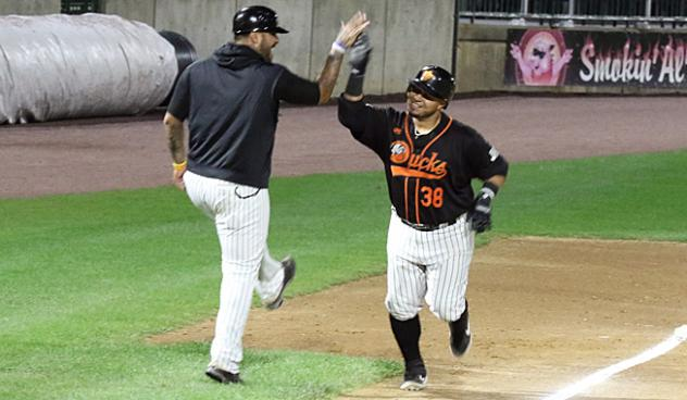 Ramon Cabrera of the Long Island Ducks gets a high five from Hector Sanchez as he rounds the bases