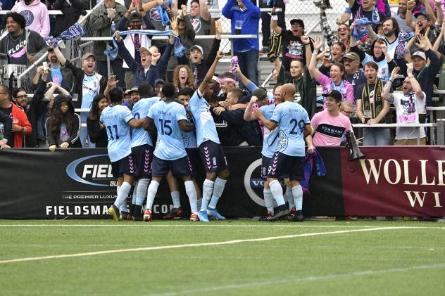 Forward Madison FC celebrates a goal with its fans