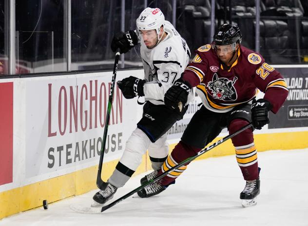Jake Walman of the San Antonio Rampage (left) eyes the puck against the Chicago Wolves