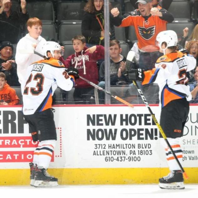 Morgan Frost of the Lehigh Valley Phantoms (left) celebrates his first goal