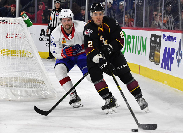 Cleveland Monsters defenseman Adam Clendening (right) vs. the Laval Rocket