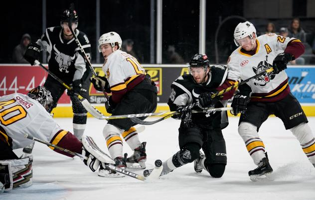 Nick Lappin of the San Antonio Rampage (in black) battles for a puck in front of the Chicago Wolves net