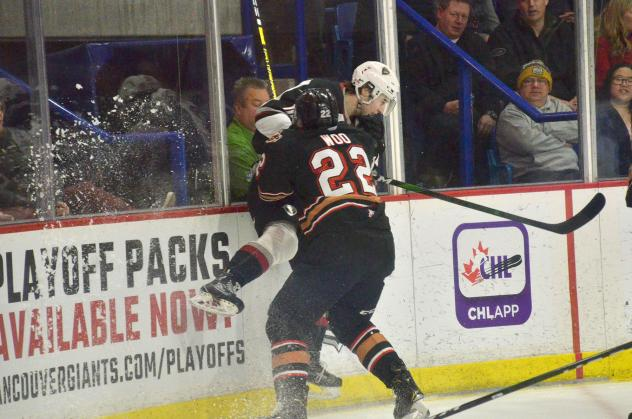Vancouver Giants get slammed against the boards by the Calgary Hitmen