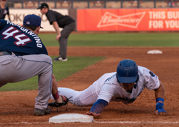 Romer Cuadrado of the Tulsa Drillers slides back safely into first on a pick off attempt