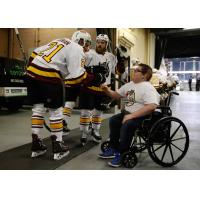Scooter Vaughan of the Chicago Wolves greets young fan Blake Burriss