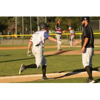 Blake Baumgartner extends a hi-five to Medford Rogues' third base coach Mike Takamori