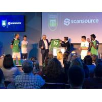 Greenville Triumph Head Coach John Harkes presents Scansource CEO Mike Bauer with the team's new jersey