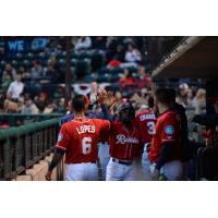 Shed Long gets high fives in the Tacoma Rainiers dugout