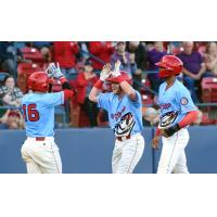 Blaine Crim of the Spokane Indians receives high fives after one of his home runs
