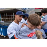Mark Contreras of the Pensacola Blue Wahoos signs the shirt of a young fan