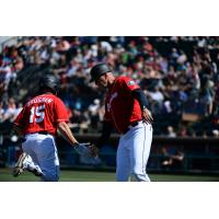 Jaycob Brugman of the Tacoma Rainiers gets a low five as he rounds the bases