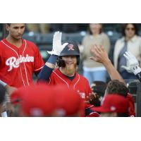 Jake Fraley of the Tacoma Rainiers receives congratulations in the dugout