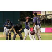 Frisco RoughRiders converse while the umpire examines his pants