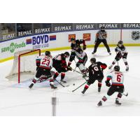 Kelowna Rockets try to control the puck in front of the Prince George Cougars net