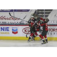 Vancouver Giants defenceman Nicco Camazzola (center) delivers a hit vs. the Prince George Cougars